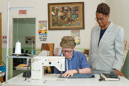 Noel Thomas, resident of the Open Arms Drop-In Centre sews a cushion cover, while Yvonne Grant looks on.