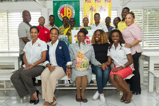Yvonne Grant (centre), founder and manager of the Open Arms Drop-In Centre for homeless men welcomes a staff delegation from the Jamaica Broilers Group and its subsidiaries Hi-Pro and The Best Dressed Chicken to the facility at 16 ½ Windward Road, Kingston. The delegation was there to deliver items which were donated by employees at the Group's local and international offices during the Valentine's Season. At front (from left) are: Danah Cameron, group public relations & training officer, at the Jamaica Broilers Group; Loren Henry-Lee, public relations & training co-ordinator, Jamaica Broilers Group; Lucean Slater, Open Arms Drop-In Centre and GeAnne Dwyer, brand officer, The Best Dressed Chicken. Back row (from left) are: Terence Melhado, resident; Garvin Abrahams, Hi-Pro technical sales representative; residents: Everton Senior, Courtney Barnes, Patrick Wildman, Peter Foster-Davis; Karla Davis, of the human resource & public relations department, Jamaica Broilers Group and project co-ordinator; residents: Dave Fuller and Lindley Griffiths; Anthony Banton, driver at The Best Dressed Chicken and Natasha Malcolm of the Open Arms Drop-In Centre.
